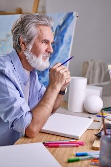 鉛筆を持った白髪の芸術家は、考えながら熟考している。家に。アート、クラフト、イマジネーションのコンセプト