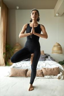 Giovane femmina dai capelli grigi a piedi nudi in activewear in piedi sul pavimento in vrikshasana o posa dell'albero, facendo yoga mattutino