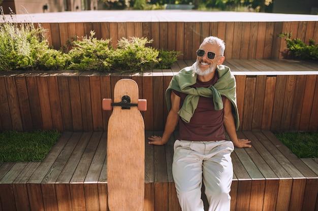 外の木製のベンチに座って幸せな笑顔で白髪のひげを生やした成熟した運動男