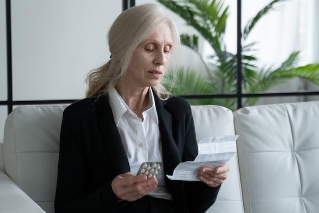 Седая пожилая женщина читает инструкцию перед приемом лекарства дома. бабушка, сидя на диване, читает инструкцию по применению таблеток.