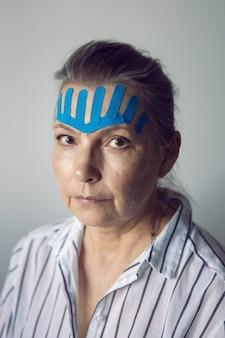 滑らかにするために彼女の顔にキネシオテープを付けた白髪の年配の女性