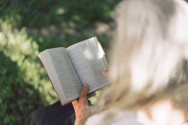 Gray-haired grandmother holds bible in her hands.