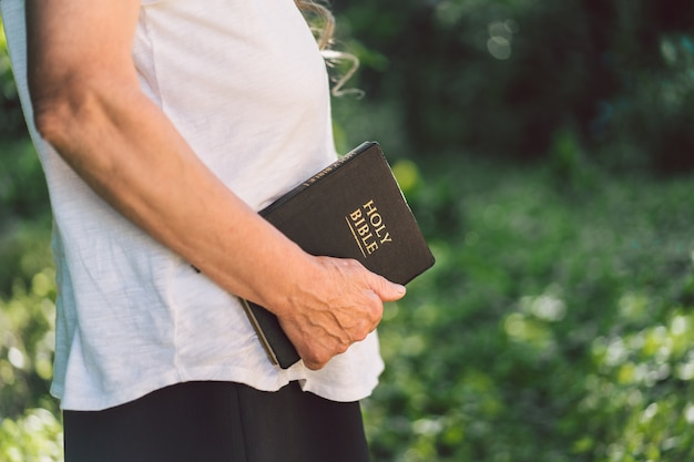 Седая бабушка держит в руках библию.