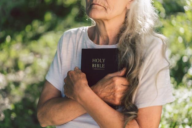 白髪の祖母は聖書を手に持っています。