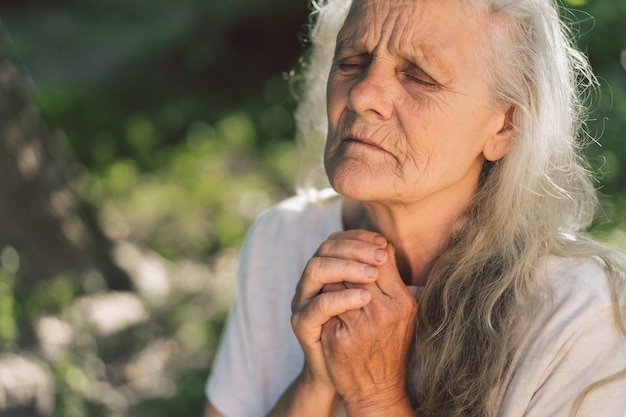 The gray-haired grandmother is praying in outdoors.