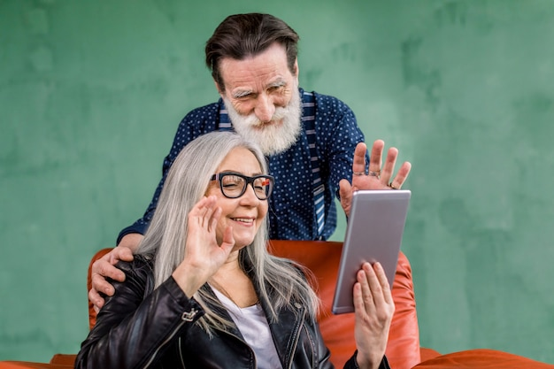 Gray haired lady holding tablet for video call, while handsome bearded husband leaning on chair and hugging her