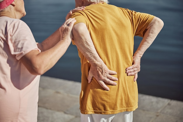 A gray-haired lady supporting her senior husband suffering from lower back pain