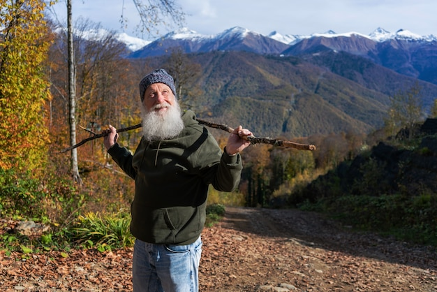 Gray-haired ld man with a beard conquers the summit, concept of tourism and recreation in old age
