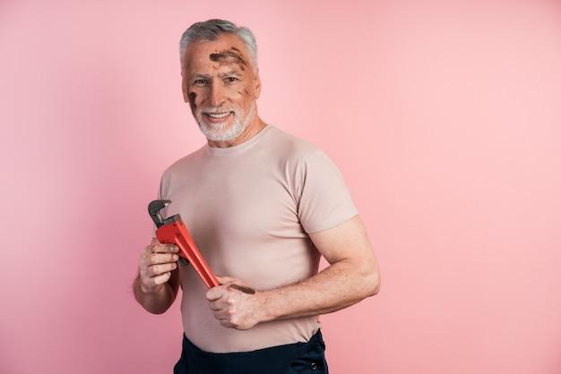 白髪の男性ビルダーは、孤立したピンクの壁にレンチを持って彼の手で微笑む