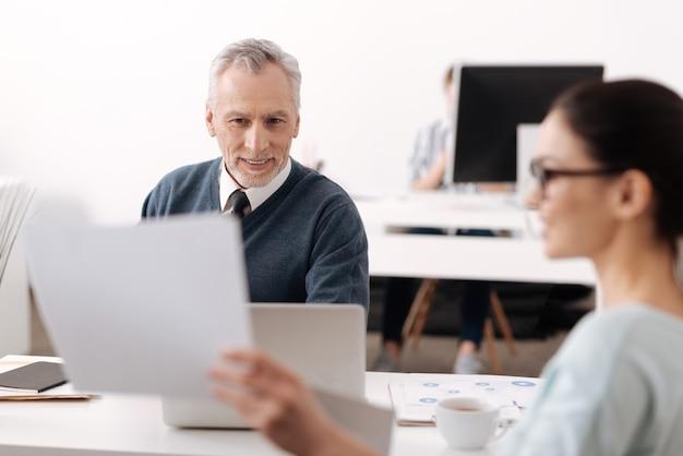 文書の情報を読みながら職場に座って笑顔を保つ白髪の男性
