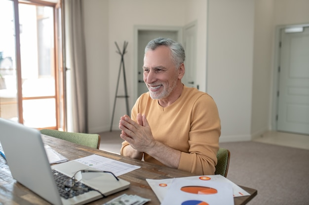 Gray-haired man in casual clothes working from home