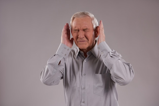 Gray haired man covers ears