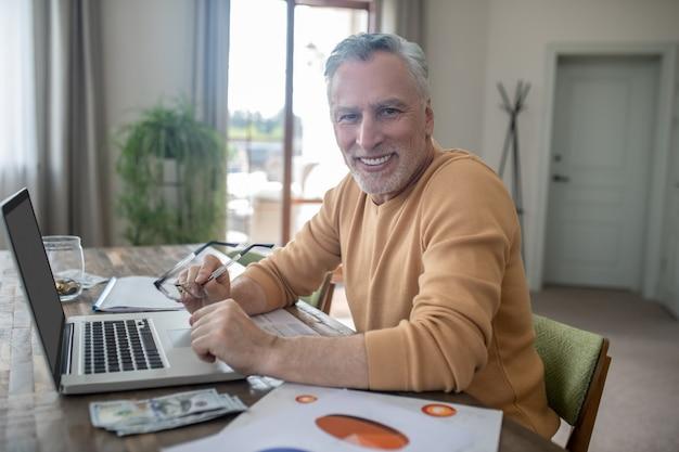 Седовласый мужчина в повседневной одежде работает из дома и выглядит довольным