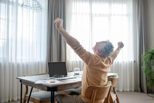 Седовласый мужчина в повседневной одежде работает из дома