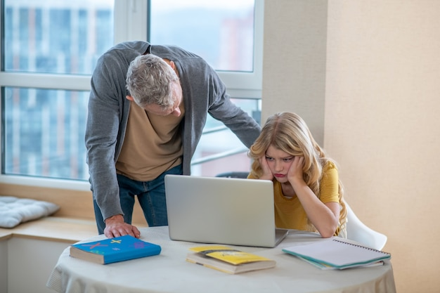 A gray-haired man standing next to his daughter while she working on the laptop