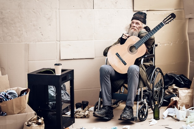A gray-haired man with beard sits near garbage with a guitar