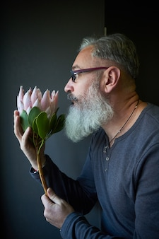 Gray-haired man with glasses and a beard holds a pink protea in his hands