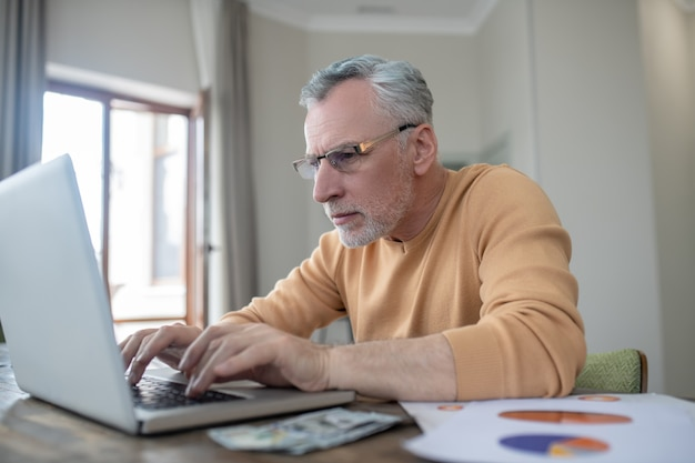 Gray-haired man working on a laptop and looking busy