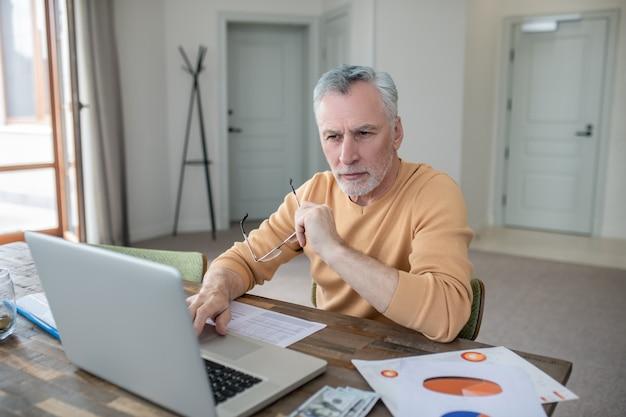 Седовласый мужчина работает на ноутбуке и выглядит занятым