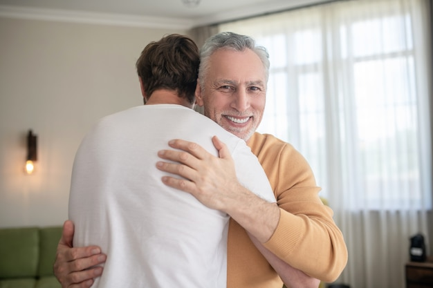 Gray-haired mature man hugging his sona and looking happy