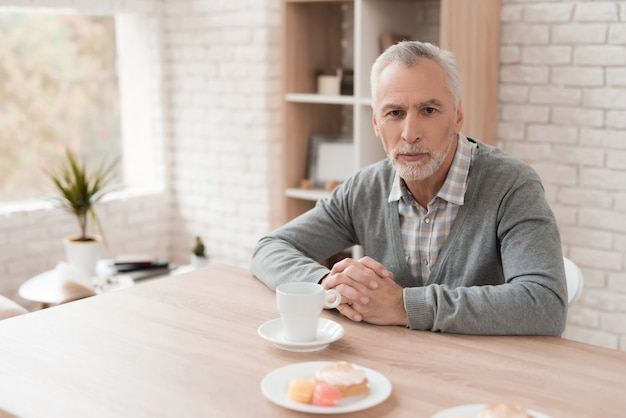 Gray haired old man is sitting at table drinking coffee