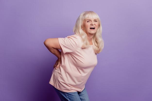 회색 머리 할머니는 보라색 배경 위에 고립 된 허리 통증을 앓고