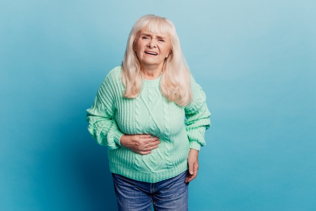 Gray haired old woman suffer stomachache over blue background