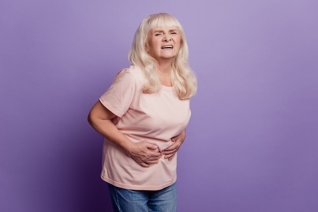 Gray haired old woman suffer stomachache over violet background