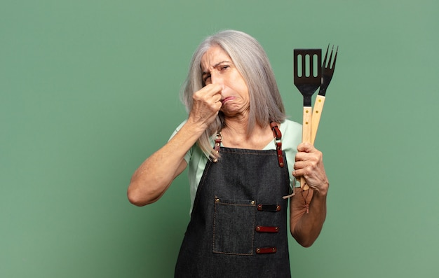 Gray haired pretty barbecue chef with kitchen tools