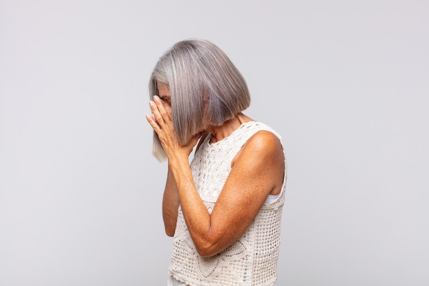 Gray haired woman covering eyes with hands with a sad, frustrated look of despair, crying, side view