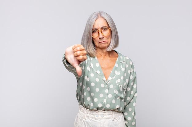 회색 머리 여자는 십자가, 화가, 짜증, 실망 또는 불쾌감을 느끼고 심각한 표정으로 엄지 손가락을 내립니다.