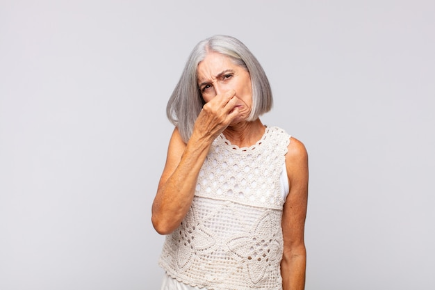 Gray haired woman feeling disgusted, holding nose to avoid smelling a foul and unpleasant stench