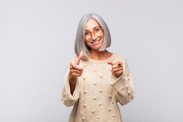 회색 머리 여자는 행복하고, 시원하고, 만족하고, 편안하고, 성공하고, 카메라를 가리키고, 당신을 선택합니다.