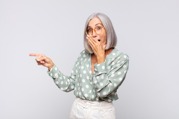 Gray haired woman feeling happy, shocked and surprised, covering mouth with hand and pointing to lateral copy space