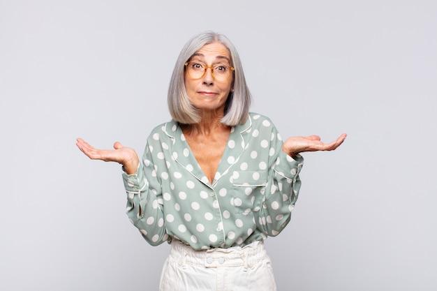 白髪の女性は困惑して混乱していると感じ、疑って、重みを付けたり、面白い表現でさまざまなオプションを選択したりします