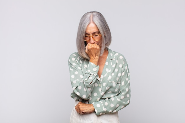 Gray haired woman feeling serious, thoughtful and concerned, staring sideways with hand pressed against chin