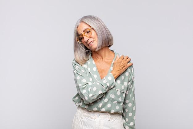 Седая женщина чувствует усталость, стресс, тревогу, разочарование и депрессию, страдает от боли в спине или шее.