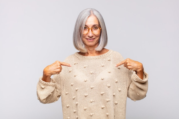 誇らしげに、前向きでカジュアルに見える白髪の女性が両手で胸を指しています