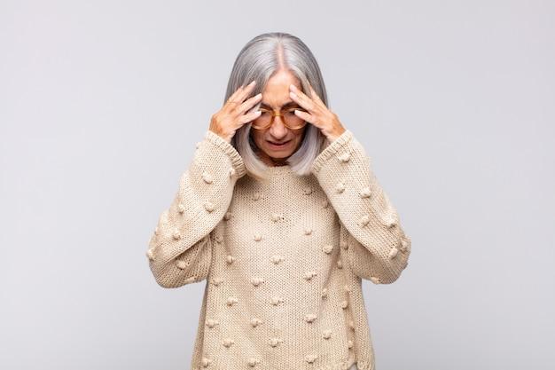 회색 머리 여자는 스트레스와 좌절감을 느끼고 두통으로 압력을 받고 문제를 겪고 있습니다.
