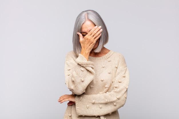 ストレス、恥ずかしがり屋、または動揺しているように見える白髪の女性、頭痛が孤立している