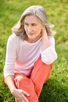 Седая женщина медитирует на зеленой лужайке