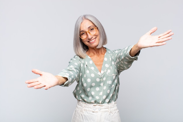 Gray haired woman smiling cheerfully giving a warm, friendly, loving welcome hug, feeling happy and adorable