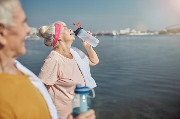그녀의 손에 플라스틱 병에서 수석 아가씨 마시는 물을보고 회색 머리 남자