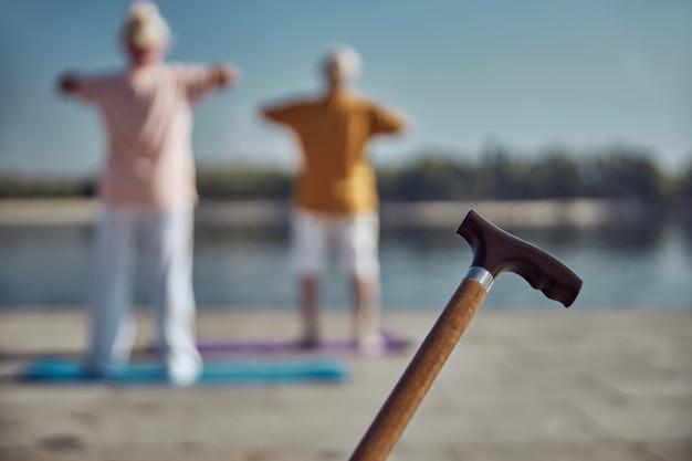灰色の頭のスポーティな男性と屋外でストレッチ運動をしている女性