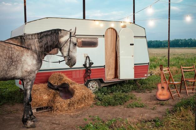 Серая лошадь, передвижной прицеп, светящаяся гирлянда, гитара, складные стулья для отдыха, тюки сена, седло и уздечка