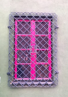 Серый дом с розовыми оконными рамами и фиолетовыми решетками в винтажном стиле