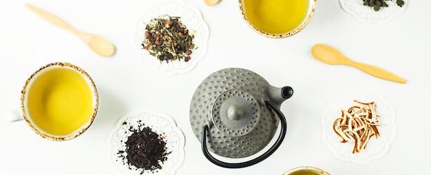 흰색 테이블에 준비 음료와 함께 건조 차와 컵의 다른 종류의 회색 철 주전자