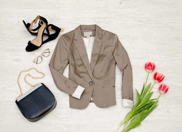 グレーのジャケット、ハンドバッグ、サングラス、靴、ピンクのチューリップ