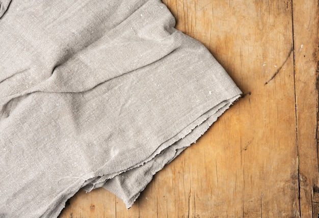Gray kitchen towel on brown wooden background, top view, copy space