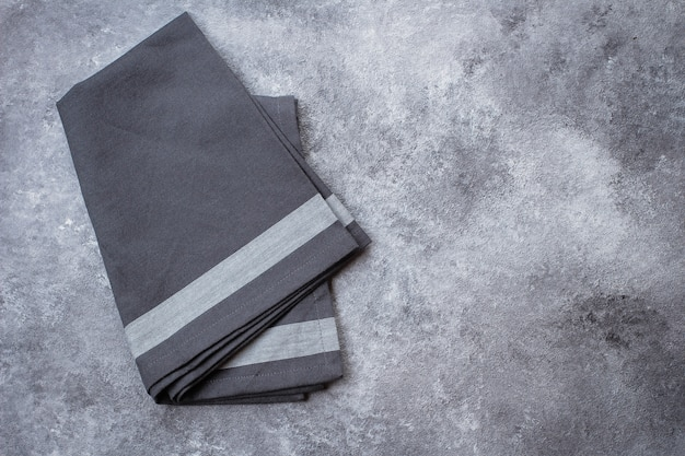 Gray kitchen towel on gray stone table background.